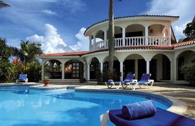 der Pool inklusive Sonnenliegen und das Poolhaus des Hotels sind sichtbar