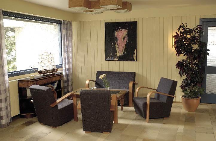 Hotellobby mit Polstermöbeln, und einem großen Fenster, schlicht gehalten und einer großen Topfpflanze