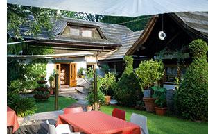 ein kleines gemuetliches Landhaus und dessen Gastgarten mit viel Gruen