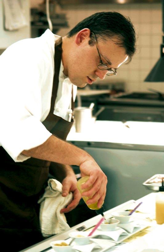 Ein Koch arbeitet mit einer Saucenspritze und verfeinert sein Gericht