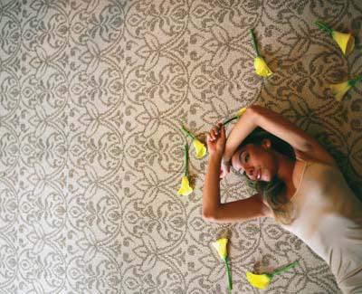 eine junge frau liegt zwischen gelben blumen mit über dem kopf verschränkten armen