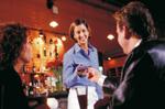 Mann und Frau im Restaurant werden beraten vom freundlichen Personal