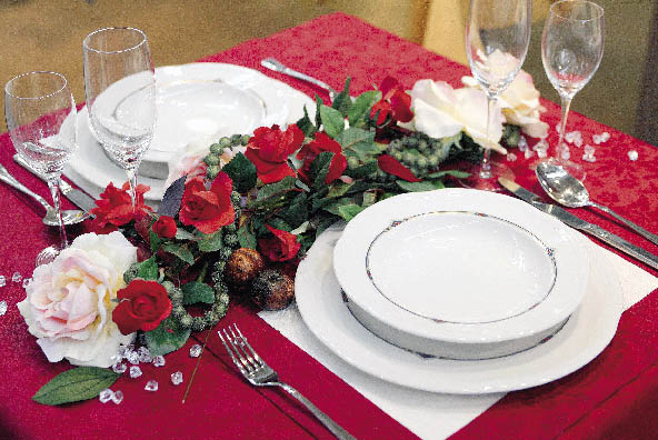 Herbstlich inspiriertes blumenarrangement schmückt einen in dunklem Rot gedeckten tisch
