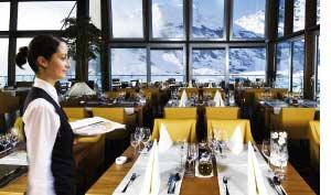Eine Kellnerin in einem Alpenrestaurant mit Panoramablick auf die Berge