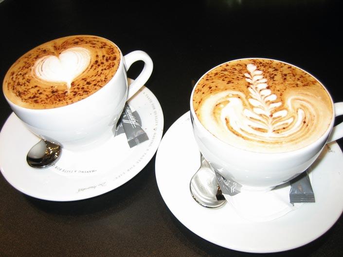 zwei Tassen Kaffee mit Herzchen im Kaffeeschaum