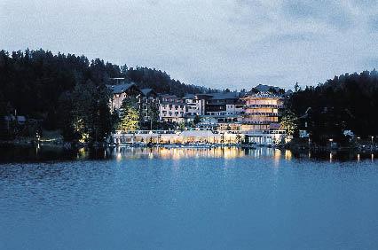 Hotel am See in der Abenddämmerung in einem Meer aus lichtern die sich im See wiederspiegeln