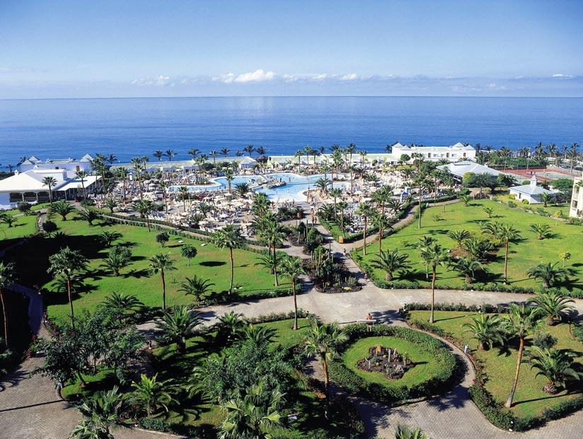 eine Massive Hotelanlage am Strand mit viel Grünfläche, einem Pool und diversen Freizeitaktivitäten darunter ein Tennisplatz