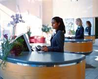 eine Dame steht an der Rezeption hinter ihrem Computer