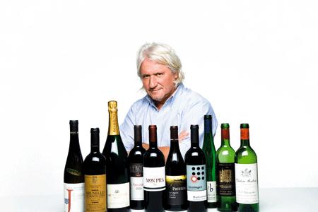 ein Mann hinter einer Reihe von verschiedenen Weinflaschen