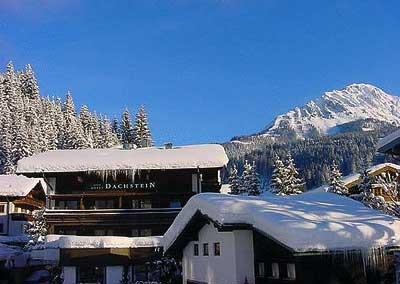 das Hotel Dachstein in Filzmoos unter einer Schneedecke beleuchtet von der Morgensonne