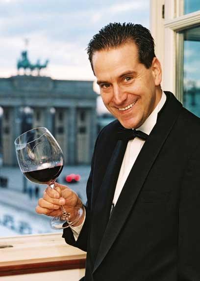 Gerhard Retter im Anzug mit einem Glas Rotwein in der Hand