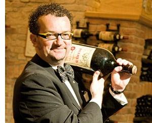 Alexander Adlgasser trägt eine Magnum Flasche Wein auf der Schulter