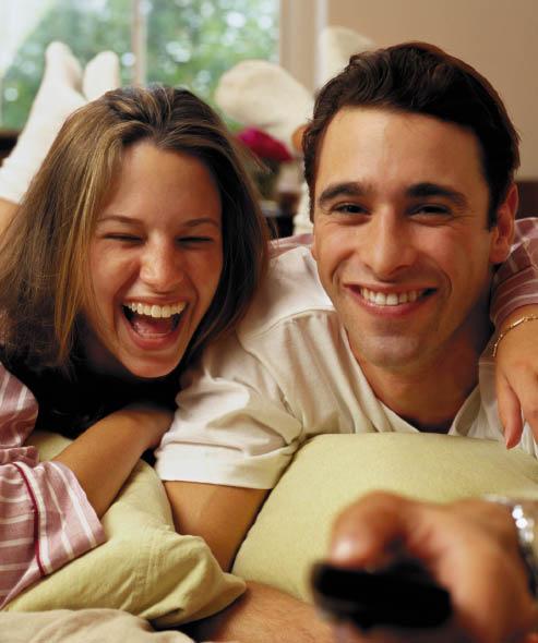 eine junge frau und ein junger herr liegen zusammen auf der couch, der Mann hält die fernbedienung in der hand und beide lachen