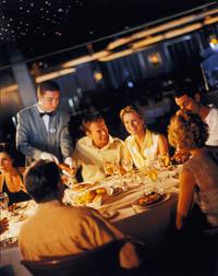 Eine Gruppe von Menschen genießt ein Abendessen in Gesellschaft während der Kellner nachschenkt