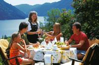 ein Tisch mit Gästen im freien mit Blick auf den See und Berge wird von einer Kellnerin bedient, alle sehen zufrieden und fröhlich aus