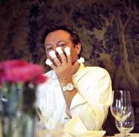 Heino Huber sitzend mit Fingerhüten an der linken Hand vors Gesicht haltend