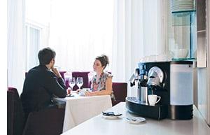 ein Vollautomat, dahinter ein Paar sitzend an einem Tisch, vertieft in eine Unterhaltung