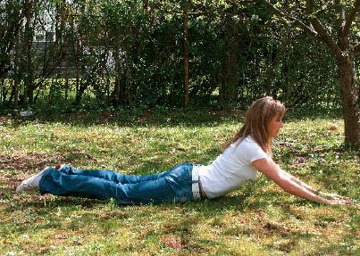 eine Dame liegt im Graz und demonstriert die Entspannungs- und Yogaübung die Kobra.