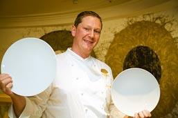 ein junger Koch hält zwei Teller in der Hand und lächelt