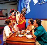eine Gruppe beim essen, während es eine Vorstellung eines traditionellen Tanzes gibt.
