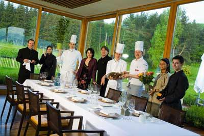 das Küchen und Gastropersonal posiert vor einem riesengroßen Panoramafenster und vor einer langen weißgedeckten Tafel