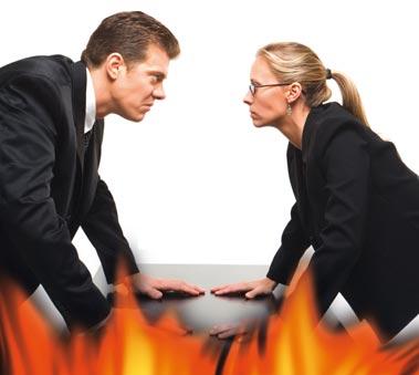 zwei Arbeitskollegen gegenüber voneinander über den Tisch gebeugt, starren sich mit bösen Blicken nieder