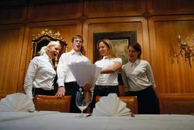 ein Herr und drei Damen besprechen den Plan der Abendgestaltung, alle tragen weiße Hemden