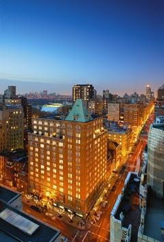 ein blauer Himmel mit rötlichen Akzenten wegen des Sonnenuntergangs und die Skyline im Stadtlicht getaucht