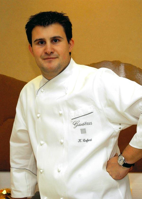 Klaus Erfort in einer weißen Kochjacke und mit einem Arm in die Hüften gestützt