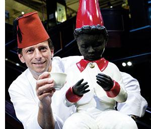 ein Superkoch mit hoher roter Kochmütze und einer schwarzen Meinl Puppe