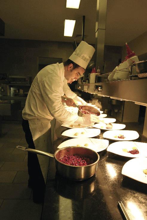 Ein Herr beim Anrichten der Teller auf dem Küchentresen