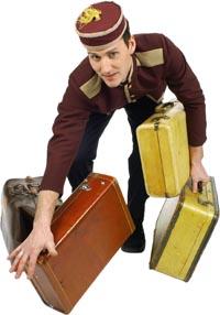 Ein Gepäckträger mit vier Koffern versucht diese auszubalancieren
