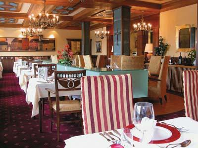 einblick in ein restaurant mit weißen tischtüchern und einem rotweiss liniertem stuhl