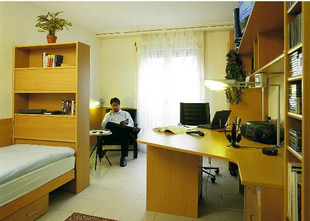 Ein mann sitzt in einem mit Holzmöbel verkleidetem Raum und liest