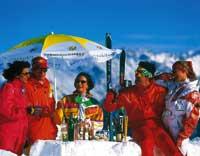 Menschen genießen das schöne Wetter und die kühlen Drinks auf der Skihütte unter strahlend blauem himmel