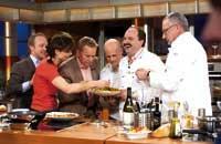 eine Gruppe von TV-Köchen bestaunen ein Gericht