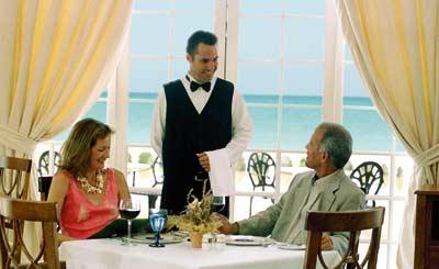 ein Liebespaar sitzt in einem Restaurant am Strand und wird von einem Kellner bedient, im Hintergrund ist tuerkisfarbenes Wasser zu sehen