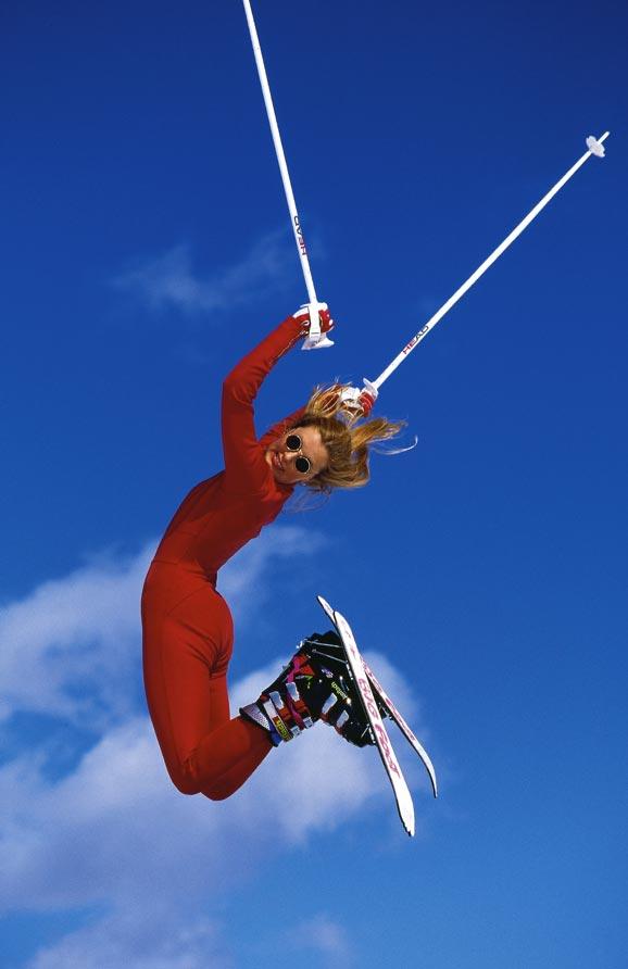 Eine Frau im roten Skianzug und Sonnenbrille springt mit Skiern und Skistöcken so hoch sie kann