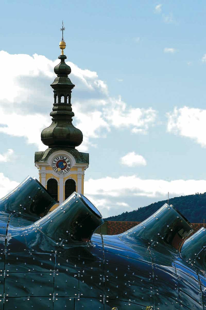 Der Ausschnitt einer Kirchenuhr vor einem bewölkten Himmel
