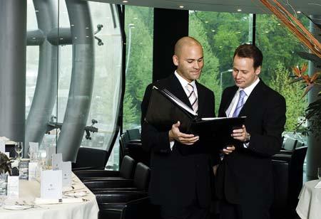zwei Herren stehen mit einer schwarzen Mappe in der Hand und unterhalten sich