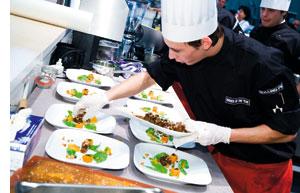 ein junger koch arbeitet hoechstkonzentriert an seinem kulinarischen werk