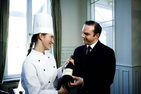 eine Dame in Kochgewand übergibt einem Herren in einem Anzug eine Champagnerflasche
