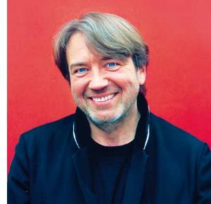 ein Mittelalter Herr mit einem symphatischen Lächeln sitzend vor einer roten Wand