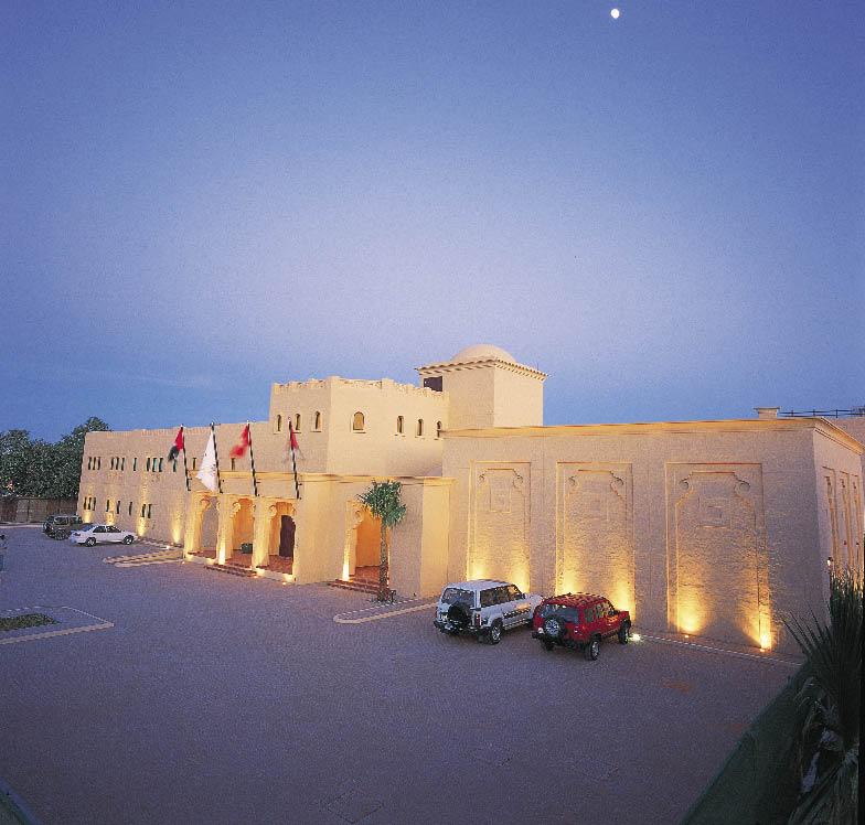 ein bauwerk im arabischen stil mit zwei parkenden autos davor und romantischer hintergrund beleuchtung