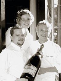 zwei Männer und eine Frau in weißer Kleidung und einer Magnum Flasche posieren lächelnd für das Bild