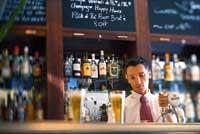 ein junger Herr steht hinter der Bar