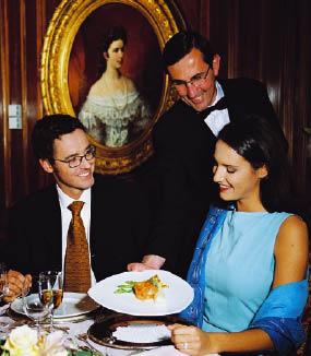 ein Liebespaar sitzt im Restaurant, der Kellner bringt der Dame ihr Gericht. Alle lächeln