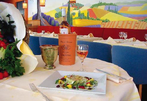 ein Tisch eingedeckt, mit einer gekühlten Falsche Rose Wein und einer bunten Kreation auf dem Teller
