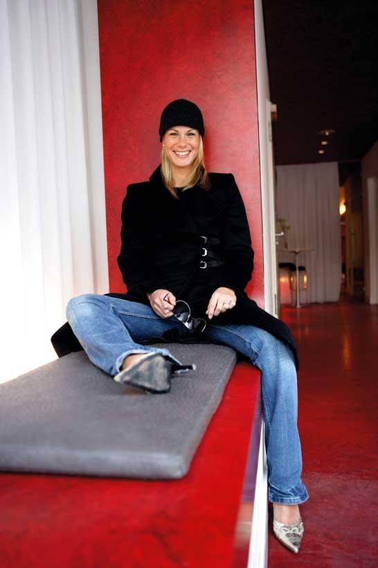 eine hübsche junge blonde frau sitzt an einem roten Fensterbrett und sieht lächelnd in die Linse, sie trägt einen schwarzen Mantel und eine schwarze Haube