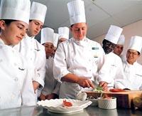 das Küchenteam sieht dem Meister bei der Arbeit zu, alle sind um den Koch versammelt,